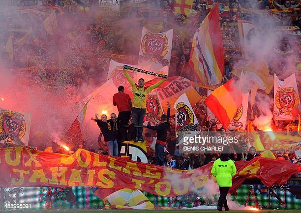 Lens' supporters light flares and cheer for their team during the French L2 football match between Lens and Brest at Felix Bollaert stadium in Lens...