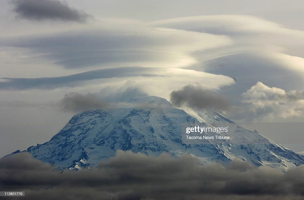 Lenticular clouds form over Mount Rainier while lower elevation clouds move over the Puyallup valley in Washington on December 3, 2008.