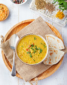 Lentil soup with bread in a ceramic white bowl on a wooden background Top view