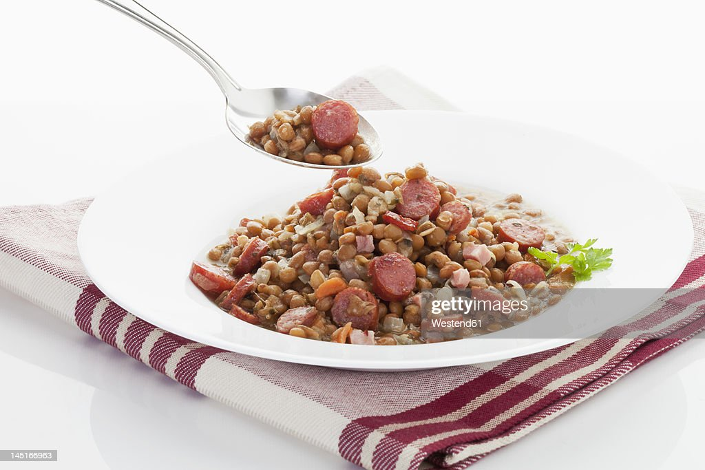 Lentil with sausage in plate on napkin