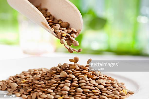 Lentils pouring from wooden scoop, close up