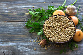Lentils with onion, garlic and parsley on a wooden table for a delicious vegan dish, rustic style, selective focus, horizontal