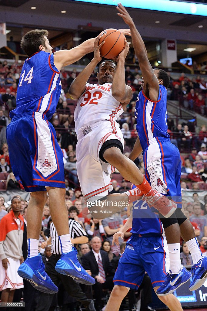 Lenzelle Smith, Jr. #32 of the Ohio State Buckeyes is fouled as he drives to the basket as Jesse Reed #14 of the American University Eagles and Darius Gardner #0 of the American University Eagles defend on November 20, 2013 at Value City Arena in Columbus, Ohio. Ohio State defeated American 63-52.