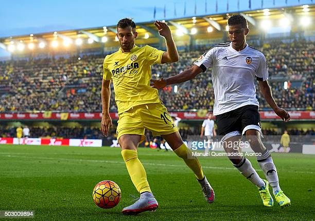 Leo Baptistao of Villarreal competes for the ball with Aderlan Santos of Valencia during the La Liga match between Villarreal CF and Valencia CF at...