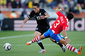 Leo Bertos of New Zealand evades the tackle by Claudio Morel of Paraguay during the 2010 FIFA World Cup South Africa Group F match between Paraguay...