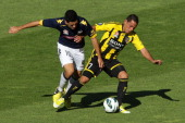 Leo Bertos of the Phoenix holds off the defence of Tomas Rogic of the Mariners during the round 12 ALeague match between the Wellington Phoenix and...