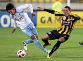 Leo Bertos of the Phoenix is hit heavily in a challenge from Hirofumi Moriyasu of Sydney during the round six ALeague match between the Wellington...