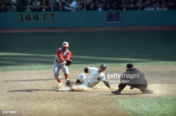 Leo Cardenas of the Cincinnati Reds reaches for throw as Clete Boyer of the New York Yankees slides safely into second during the World Series at...