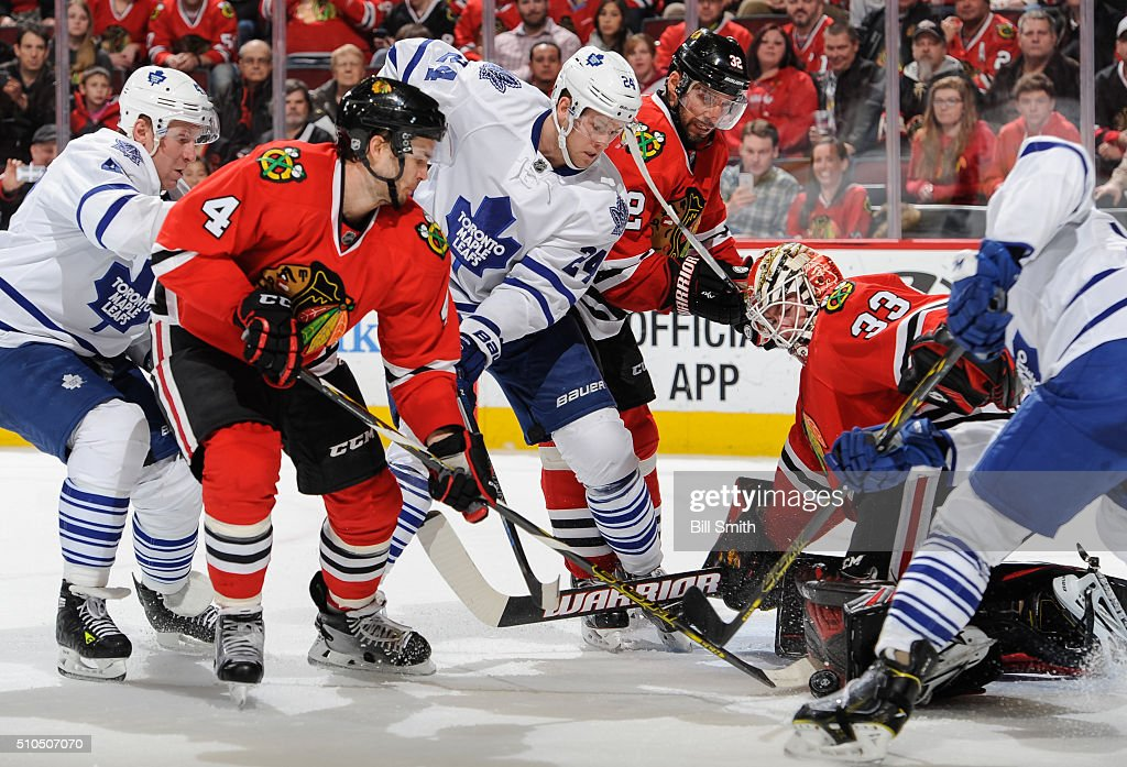 Leo Komarov #47 and Peter Holland #24 of the Toronto Maple Leafs battle for the puck with Niklas Hjalmarsson #4 and Michal Rozsival #32 of the Chicago Blackhawks, in front of goalie Scott Darling #33, in the third period of the NHL game at the United Center on February 15, 2016 in Chicago, Illinois.