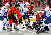 Leo Komarov and Peter Holland of the Toronto Maple Leafs battle for the puck with Niklas Hjalmarsson and Michal Rozsival of the Chicago Blackhawks in...