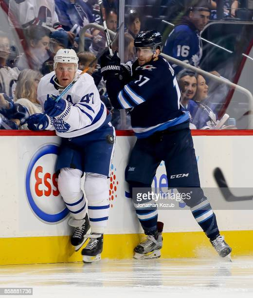 Leo Komarov of the Toronto Maple Leafs and Adam Lowry of the Winnipeg Jets eye the flying puck during third period action at the Bell MTS Place on...