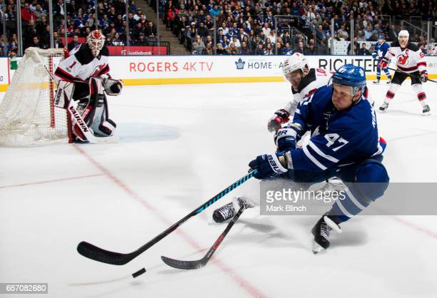 Leo Komarov of the Toronto Maple Leafs and Ben Lovejoy of the New Jersey Devils head into the corner for the puck during the third period at the Air...
