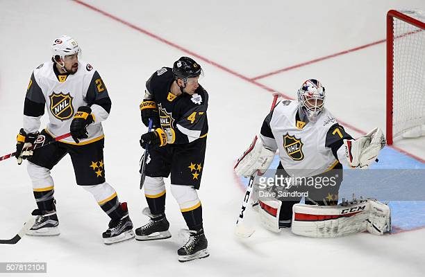 Leo Komarov of the Toronto Maple Leafs and Justin Faulk of the Carolina Hurricanes look back as goaltender Braden Holtby of the Washington Capitals...