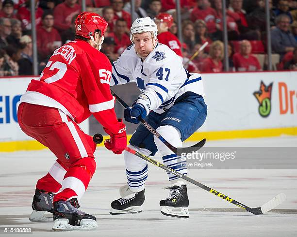 Leo Komarov of the Toronto Maple Leafs battles for the puck with Jonathan Ericsson of the Detroit Red Wings during an NHL game at Joe Louis Arena on...