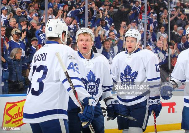 Leo Komarov of the Toronto Maple Leafs celebrates his first period goal against the Buffalo Sabres with Nazem Kadri and Connor Brown during an NHL...