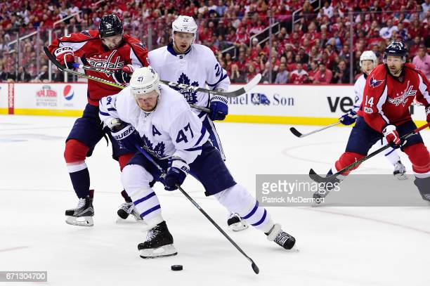 Leo Komarov of the Toronto Maple Leafs controls the puck against Evgeny Kuznetsov of the Washington Capitals in the third period in Game Five of the...