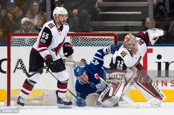 Leo Komarov of the Toronto Maple Leafs falls between Jason Demers of the Arizona Coyotes and Antti Raanta of the Arizona Coyotes during the third...