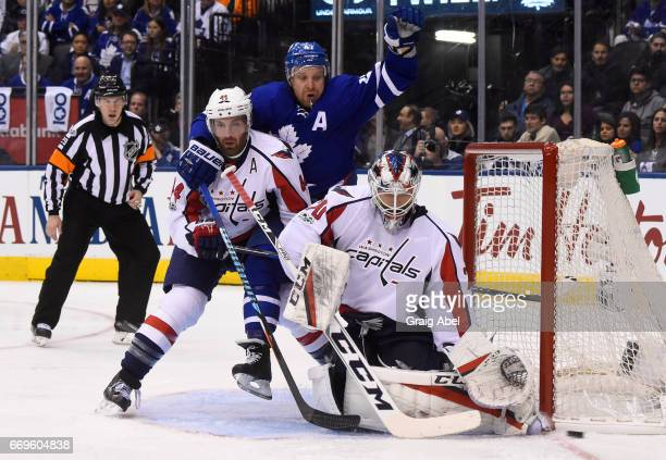 Leo Komarov of the Toronto Maple Leafs fights for space in front of Braden Holtby of the Washington Capitals with Brooks Orpik of the Washington...