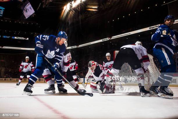 Leo Komarov of the Toronto Maple Leafs goes to the net against Nico Hischier and Cory Schneider of the New Jersey Devils during the first period at...