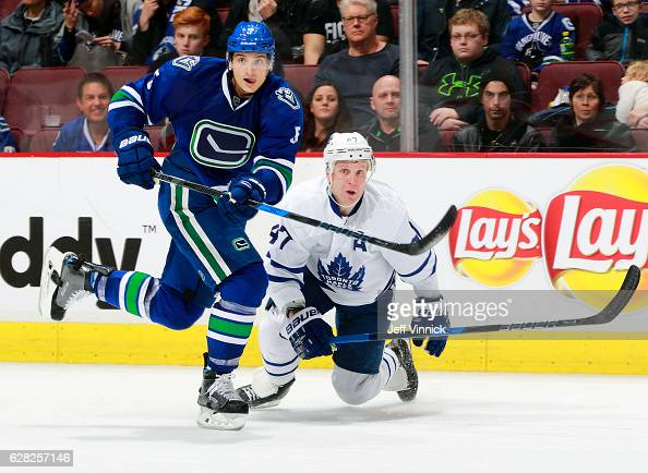 Leo Komarov of the Toronto Maple Leafs looks on as Luca Sbisa of the Vancouver Canucks passes the puck up ice during their NHL game at Rogers Arena...