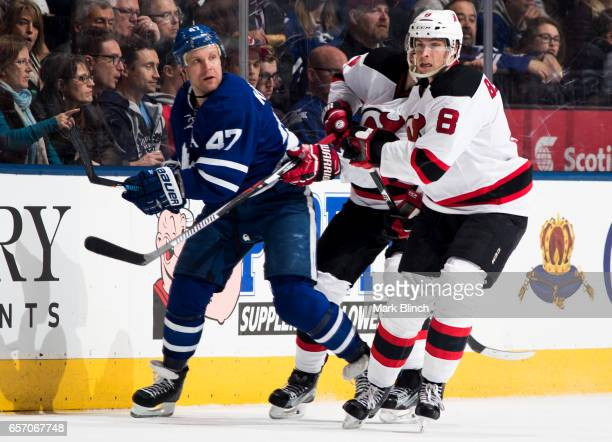 Leo Komarov of the Toronto Maple Leafs skates against Beau Bennett of the New Jersey Devils during the second period at the Air Canada Centre on...