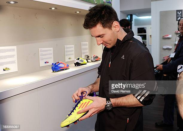 Leo Messi checks an old f50 Messi boots during his visit to the new adidas Messi Gallery on March 6 2013 in Barcelona Spain