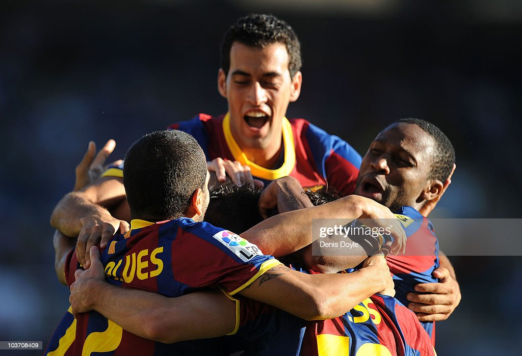 Leo Messi (unseen) of Barcelona celebrates with Seydou Keita (R) and Dani Alves after scoring Barcelona's first goal during the La Liga match between Racing Santander and Barcelona at El Sardinero stadium on August 29, 2010 in Santander, Spain.