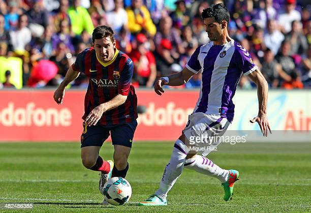 Leo Messi of FC Barcelona competes for the ball with Javier Guerra of Real Valladolid CF during La Liga match 27 between Real Valladolid CF and FC...