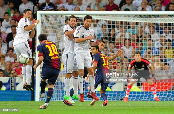 Leo Messi of FC Barcelona strikes a penalty while Cristiano Ronaldo Gonzalo Higuain and Xabi Alonso of Real Madrid attempt to block during the...