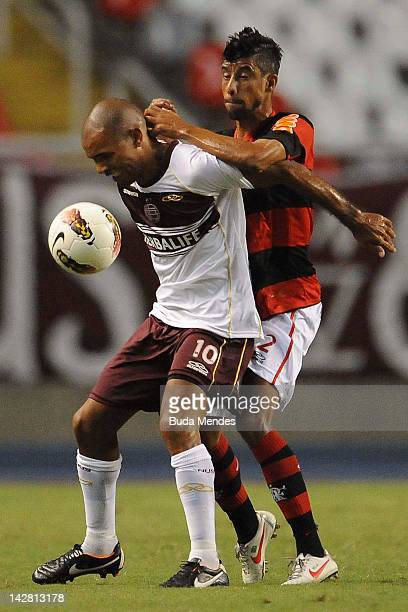 Leo Moura of Flamengo struggles for the ball with Mario Ignacio Regueiro of Lanus during a match between Flamengo and Lanus as part of the Copa...