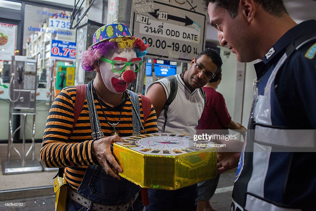 Leo Oner, a member of FTPA, has his fortune told by a Thai entertainer dressed as a clown on Pattaya's Walking Street on July 31, 2014 in Pattaya, Thailand. Since 2002, members of the Foreign Tourist Police Assistants (FTPA) of Pattaya have been assisting local police on Walking Street, Pattaya's main nightlife area. Members of the FTPA carry handcuffs, batons, and pepper spray, and are charged primarily with assisting foreign visitors and the Thai police, as well as breaking up fights and catching thieves.