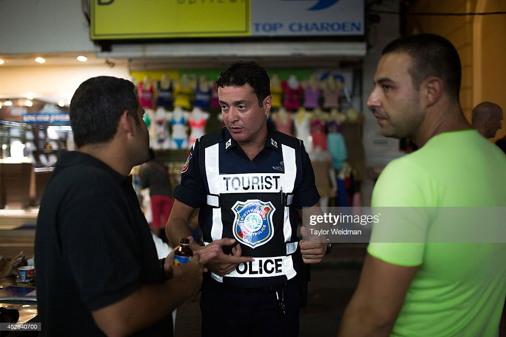 Leo Oner, a member of FTPA, talks with foreign tourists on Pattaya's Walking Street on July 31, 2014 in Pattaya, Thailand. Since 2002, members of the Foreign Tourist Police Assistants (FTPA) of Pattaya have been assisting local police on Walking Street, Pattaya's main nightlife area. Members of the FTPA carry handcuffs, batons, and pepper spray, and are charged primarily with assisting foreign visitors and the Thai police, as well as breaking up fights and catching thieves.