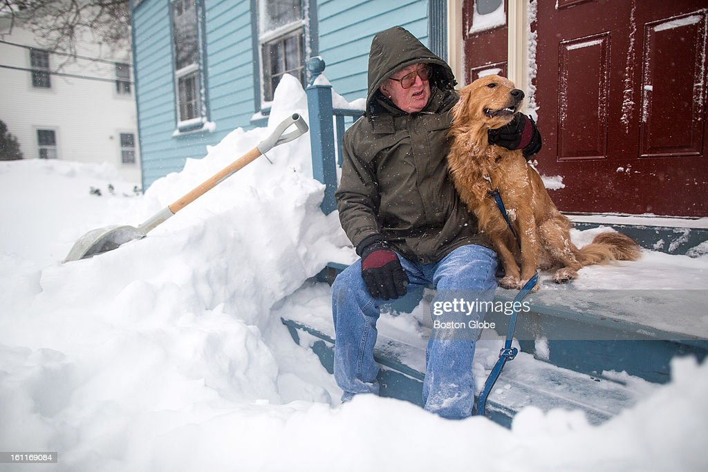 Leo Quinn took a break from shoveling the snow in front of his home to pet his neighbor's dog Teddy in Newburyport as a large winter storm hit the region.