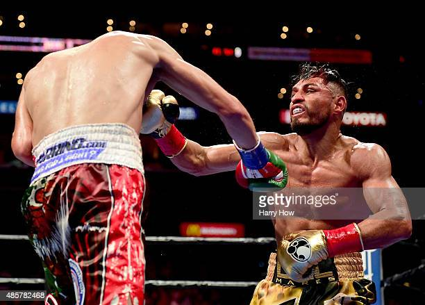 Leo Santa Cruz punches Abner Mares of Mexico during the ninth round of the WBC diamond featherweight and WBA featherweight championship bout at...