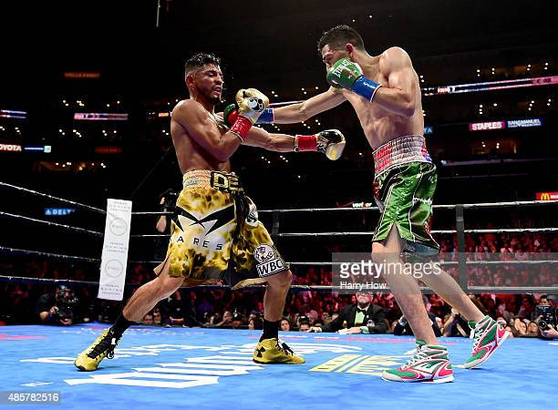 Leo Santa Cruz punches Abner Mares of Mexico during the seventh round of the WBC diamond featherweight and WBA featherweight championship bout at...