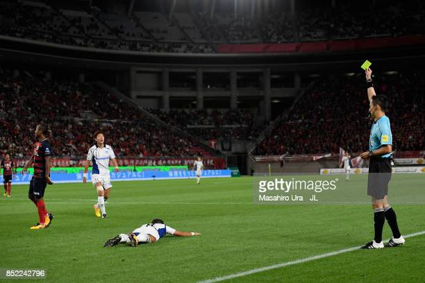 Leo Silva of Kashima Antlers is shown a yellow card by referee during the JLeague J1 match between Kashima Antlers and Gamba Osaka at Kashima Soccer...