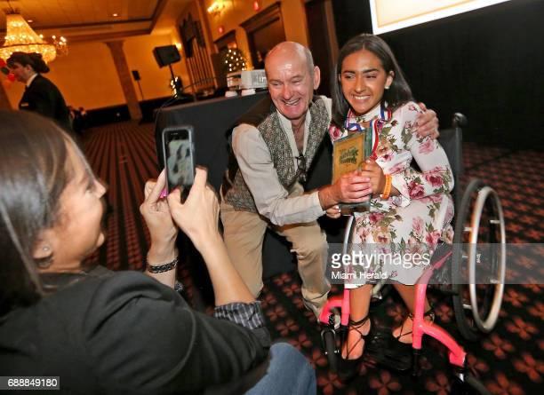 Leo Suarez/Walter Krietsch Courage Award cowinner Cypress Bay's Isabella Matos gets a hug from her coach Joseph Monks as her mother Kathy Matos gets...