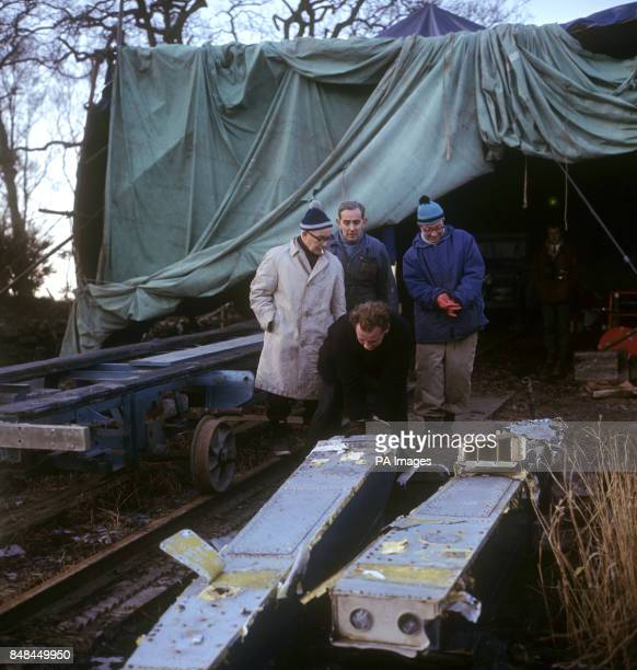 Leo Villa chief mechanic and friends of Donald Campbell with shattered sponsons of illfated 'Bluebird' recovered from Coniston Water where Campbell...