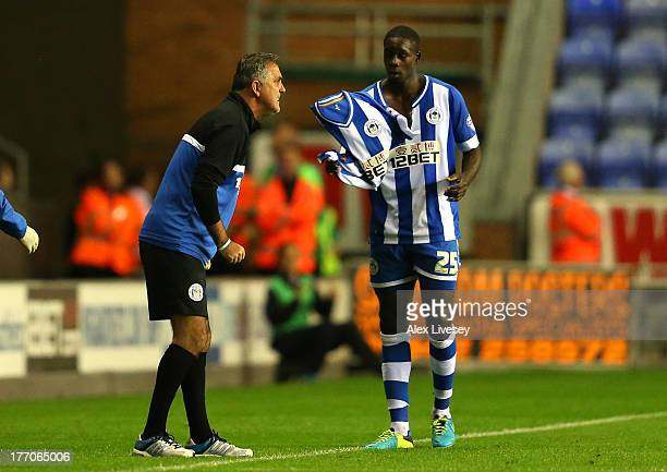 Leon Barnett of Wigan Athletic changes his shirt after ripping it apart as he celebrated scoring the equalising goal as Owen Coyle the manager of...