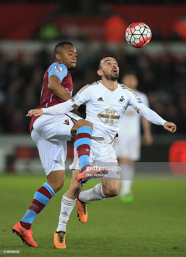 Leon Britton of Swansea City and Jordan Ayew of Aston Villa compete for the ball during the Barclays Premier League match between Swansea City and Aston Villa at Liberty Stadium on March 19, 2016 in Swansea, United Kingdom.