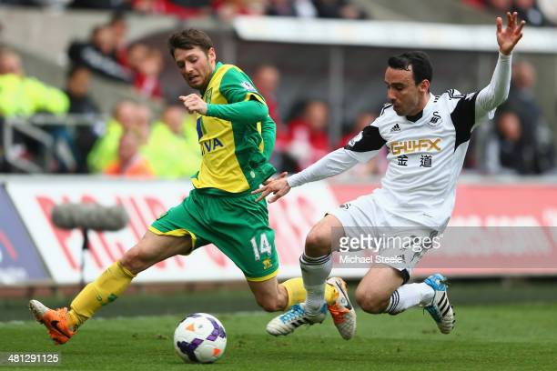 Leon Britton of Swansea City challenges Wes Hoolahan of Norwich City during the Barclays Premier League match between Swansea City and Norwich City...