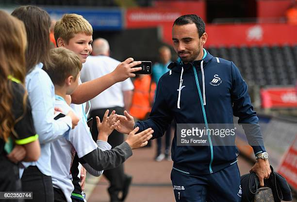 Leon Britton of Swansea City greets fans as he arrives prior to the Premier League match between Swansea City and Chelsea at Liberty Stadium on...