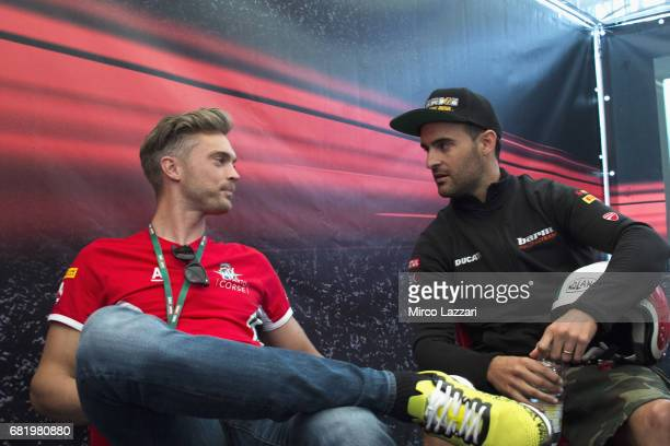 Leon Camier of Great Britain and MV Augusta Reparto Corse speaks with Xavi Fores of Spain and Barni Racing Team during the Paddock Show during the...