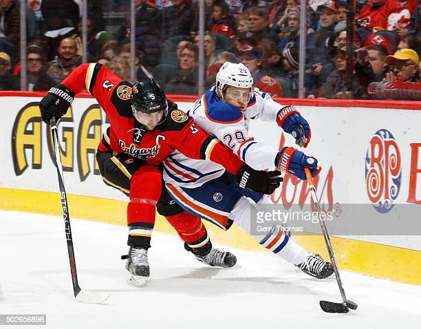 Leon Draisaitl of the Edmonton Oilers battles against Mark Giordano of the Calgary Flames at Scotiabank Saddledome on December 27 2015 in Calgary...