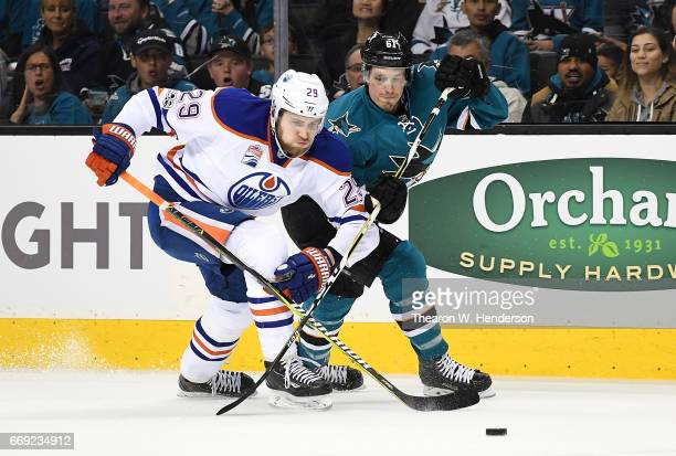 Leon Draisaitl of the Edmonton Oilers battles for control of the puck with Justin Braun of the San Jose Sharks during the first period in Game Three...