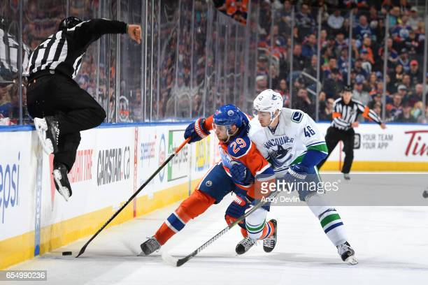 Leon Draisaitl of the Edmonton Oilers battles for the puck against Jayson Megna of the Vancouver Canucks on March 18 2017 at Rogers Place in Edmonton...