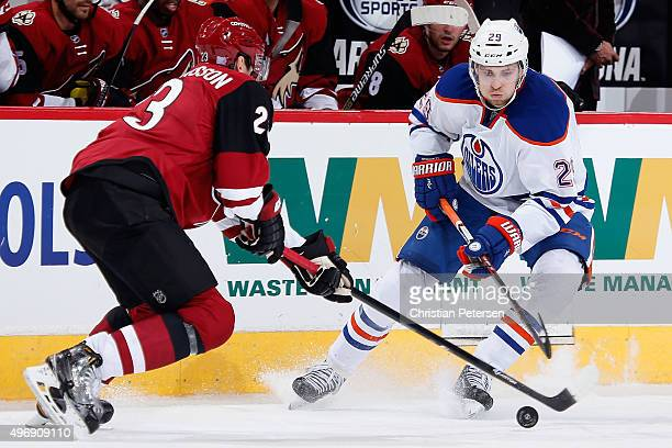Leon Draisaitl of the Edmonton Oilers controls the puck under pressure from Oliver EkmanLarsson of the Arizona Coyotes during the NHL game at Gila...
