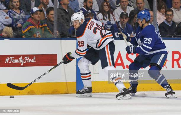 Leon Draisaitl of the Edmonton Oilers skates with the puck against William Nylander of the Toronto Maple Leafs during an NHL game at the Air Canada...