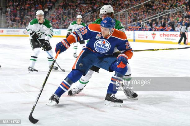 Leon Draisaitl of the Edmonton Oilers skates with the puck while pursued by Remi Elie of the Dallas Stars on March 14 2017 at Rogers Place in...