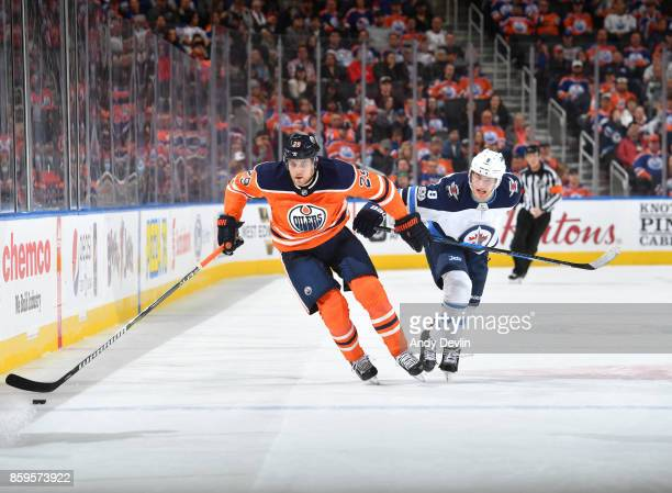 Leon Draisaitl of the Edmonton Oilers skates with the puck while being pursued by Andrew Copp of the Winnipeg Jets on October 9 2017 at Rogers Place...